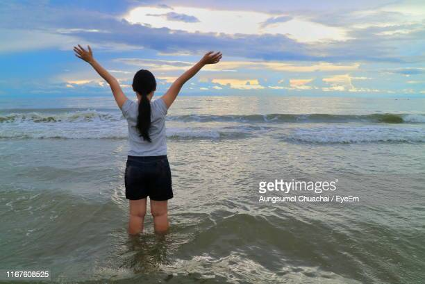 rear view of woman with arms raised standing in sea during sunset - aungsumol stock pictures, royalty-free photos & images