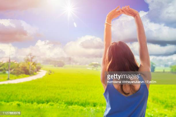 rear view of woman with arms raised standing on field against sky - vest stock photos and pictures