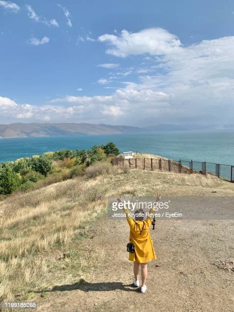 rear view of woman with arms raised standing on land against sky - jessa stock pictures, royalty-free photos & images