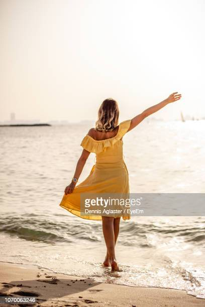 rear view of woman with arms raised while standing on beach - hands up stock photos and pictures