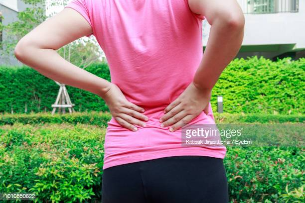 rear view of woman with backache standing against plants - backache stock pictures, royalty-free photos & images