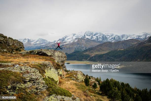Rear View Of Woman With Backpack Jumping On Mountain Against Sky