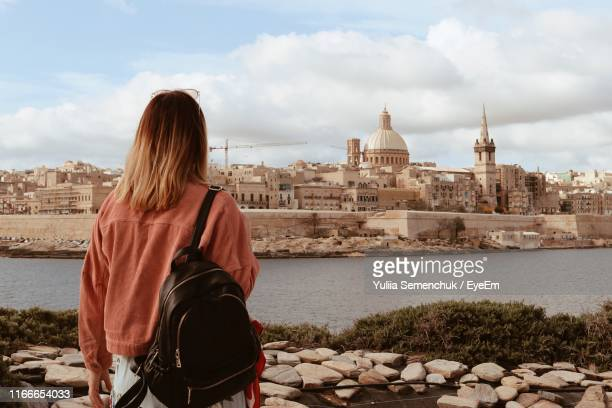 rear view of woman with backpack looking at cityscape - valletta stock pictures, royalty-free photos & images