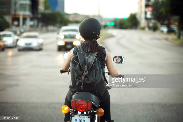 rear view of woman with backpack riding motorcycle on road - ecchi biker stock pictures, royalty-free photos & images