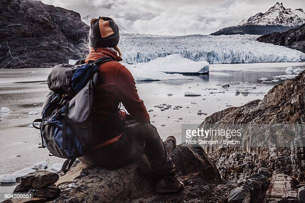 Rear View Of Woman With Backpack Sitting On Rock At Torres Del Paine National Park