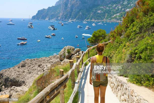 rear view of woman with backpack standing on footpath against sea - capri stock pictures, royalty-free photos & images