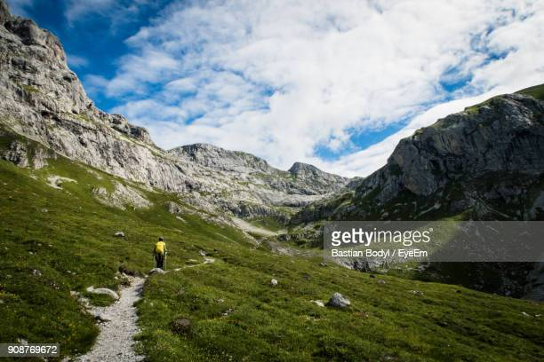 Rear View Of Woman With Backpack Standing On Mountain Against Cloudy Sky