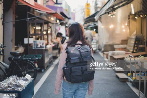 rear view of woman with backpack standing on street in city - ショッピングエリア ストックフォトと画像