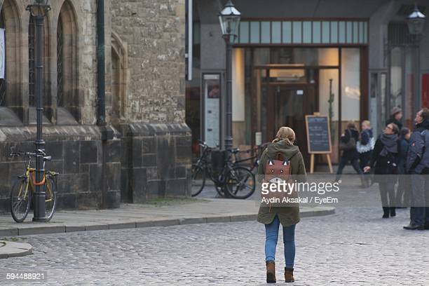 Rear View Of Woman With Backpack Walking On Street Against Building