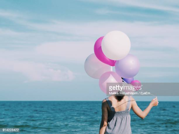 Rear View Of Woman With Balloons By Sea Against Sky