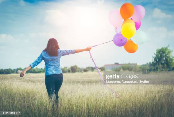 rear view of woman with balloons walking on field against sky - helium balloon stock pictures, royalty-free photos & images