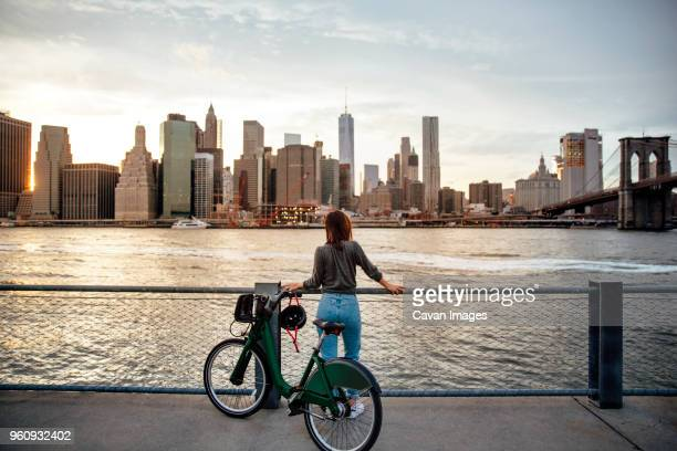rear view of woman with bicycle looking at city view while standing on observation point - new york city stock pictures, royalty-free photos & images
