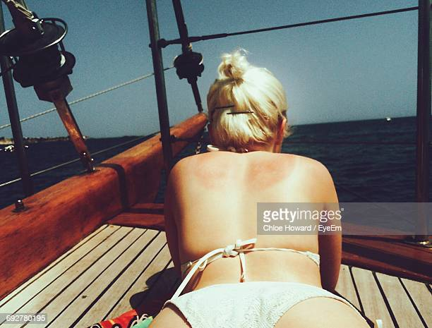 rear view of woman with bikini lying on boat in sea during sunny day - femme blonde en maillot de bain vue de dos photos et images de collection