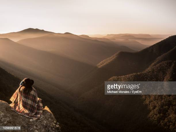 Rear View Of Woman With Blanket And Hat Looking At Mountains Against Sky