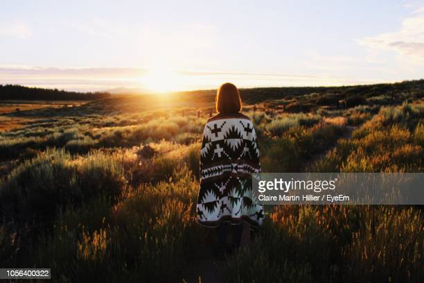 Rear View Of Woman With Blanket Standing On Field Against Sky During Sunset
