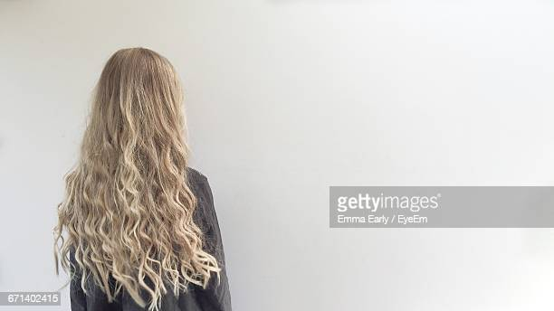 rear view of woman with blond hair against white background - langes haar stock-fotos und bilder