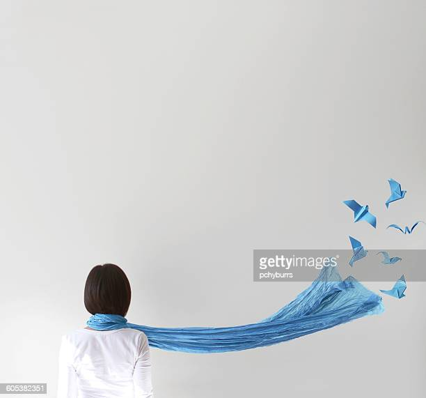 rear view of woman with blue scarf and  origami birds - waving gesture stock photos and pictures