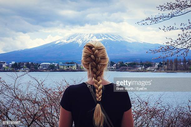 rear view of woman with braided blond hair in front of mount fuji and river - rubia espalda fotografías e imágenes de stock
