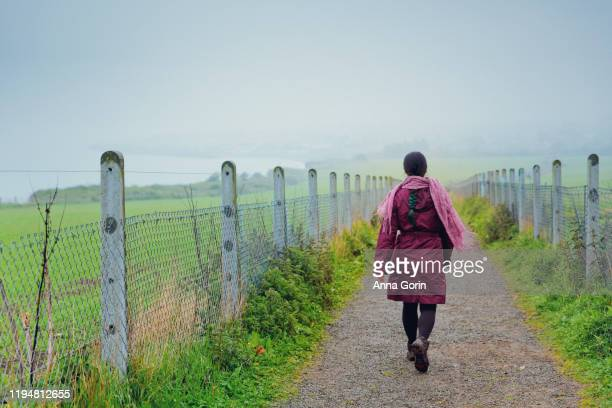 rear view of woman with braided dark hair and scarf wearing purple jacket walking down path in mist along greystones cliff walk, eastern ireland - vintage raincoat stock pictures, royalty-free photos & images