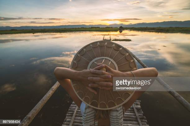 rear view of woman with burmese hat on wooden lake bridge contemplating sunset - wonderlust stock pictures, royalty-free photos & images