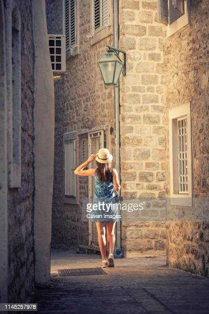 Rear view of woman with camera walking at alley amidst buildings in city