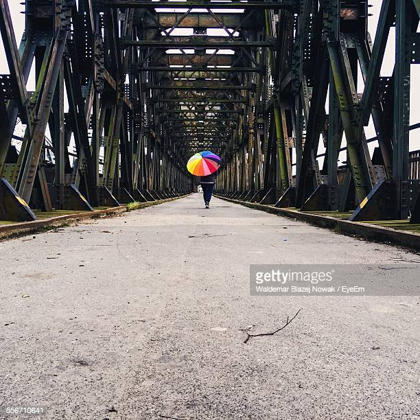rear view of woman with colorful umbrella walking on footbridge - 中距離 ストックフォトと画像