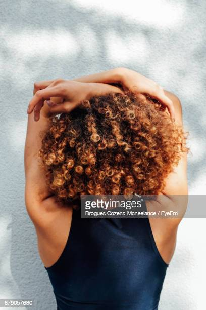 rear view of woman with curly hair against wall - curly stock pictures, royalty-free photos & images
