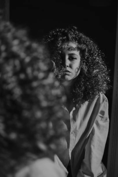 Rear View Of Woman With Curly Hair Looking In Mirror