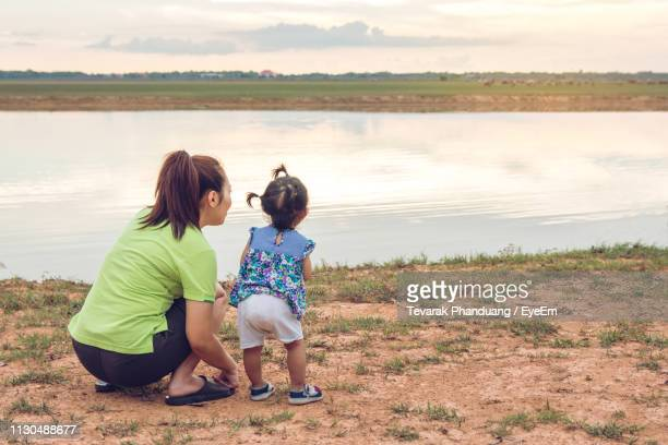 Rear View Of Woman With Daughter At Lakeshore