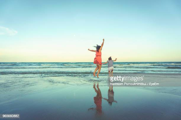 rear view of woman with daughter jumping at beach - hua hin thailand stock pictures, royalty-free photos & images