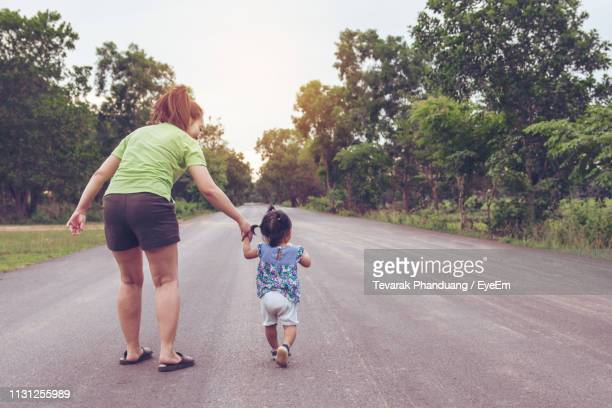 Rear View Of Woman With Daughter Walking On Road Amidst Trees