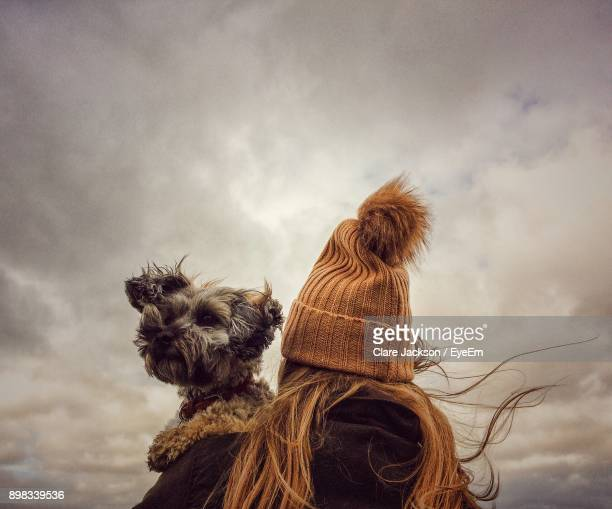 Rear View Of Woman With Dog Sitting Against Sky