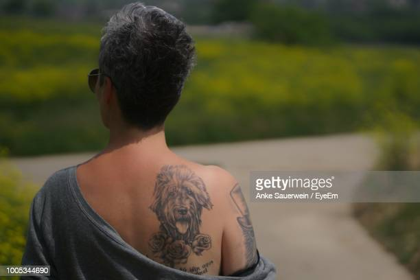 rear view of woman with dog tattoo on back - tattoo shoulder stock photos and pictures