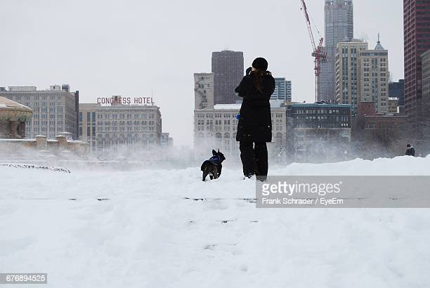 rear view of woman with dog walking on snow in city - frank schrader stock pictures, royalty-free photos & images
