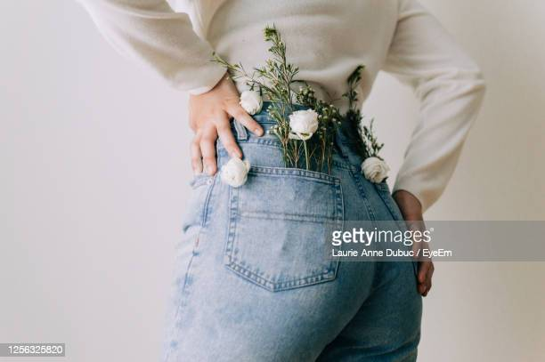 rear view of woman with flowers in pockets - denim stock pictures, royalty-free photos & images