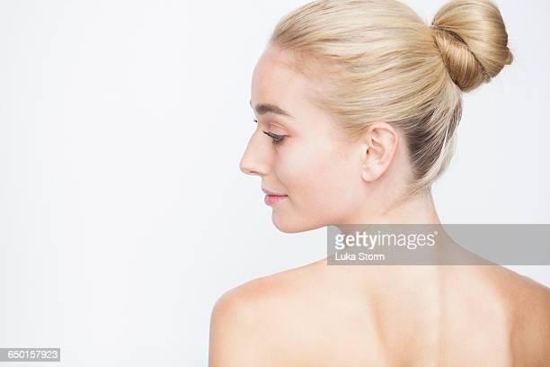rear view of woman with hair bun looking sideways smiling - coque cabelo para cima - fotografias e filmes do acervo