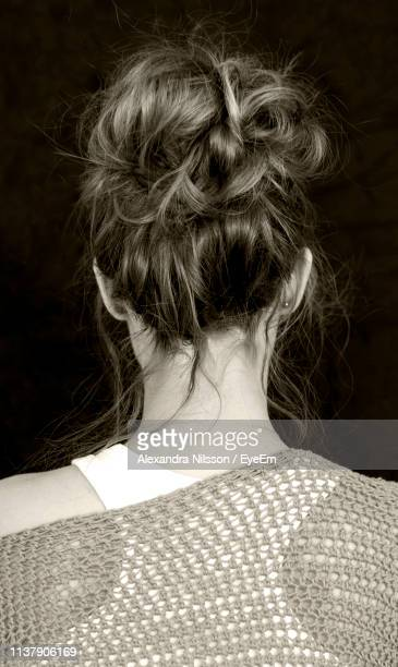 rear view of woman with hair bun over black background - おだんごヘア ストックフォトと画像