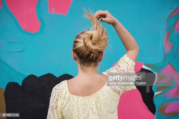 rear view of woman with hair bun standing against wall - hair bun stock pictures, royalty-free photos & images