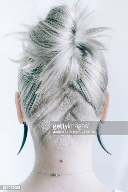Rear View Of Woman With Hairstyle Against Wall