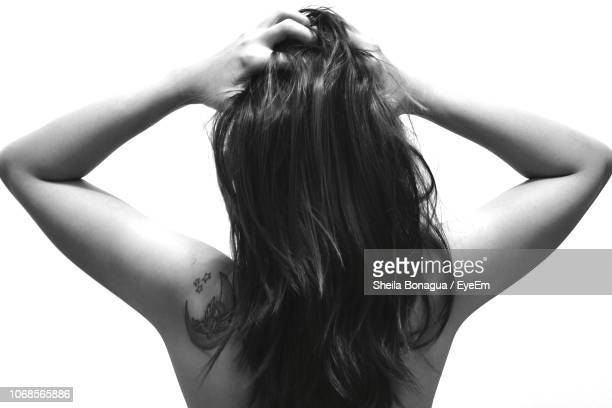 rear view of woman with hand in hair against white background - 髪に手をやる ストックフォトと画像