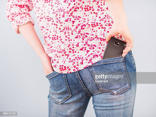 Rear view of woman with hand in pocket and mobile phone