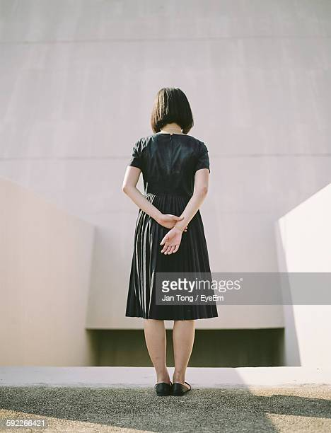 Rear View Of Woman With Hands Behind Back Standing Against Wall