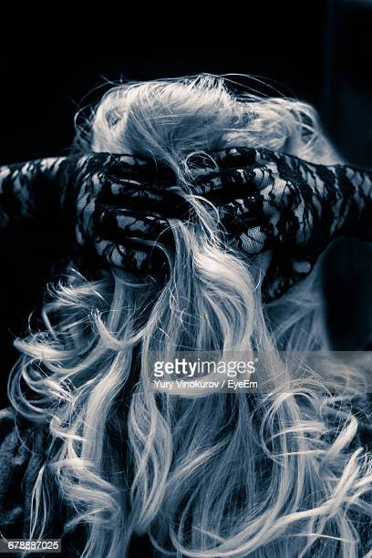 Rear View Of Woman With Hands Behind Head Against Black Background