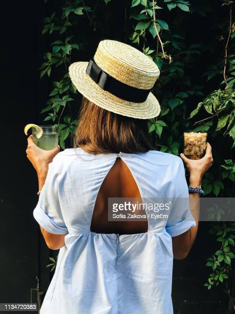 Rear View Of Woman With Hat Holding Drinks While Standing Against Plants