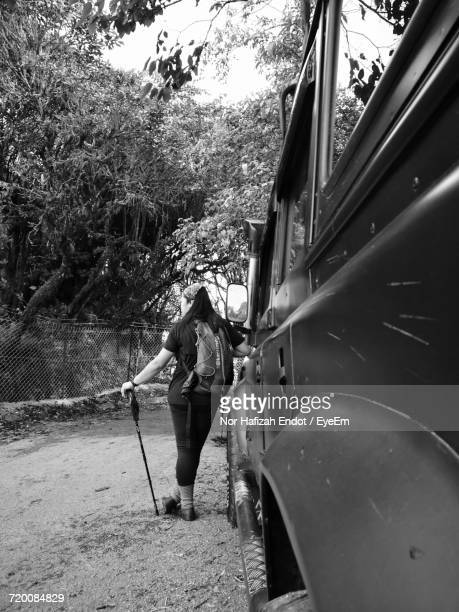 rear view of woman with hiking pole leaning on vehicle - 登山用具 ストックフォトと画像