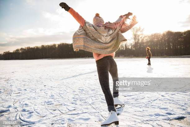 Rear view of woman with ice skates on frozen lake