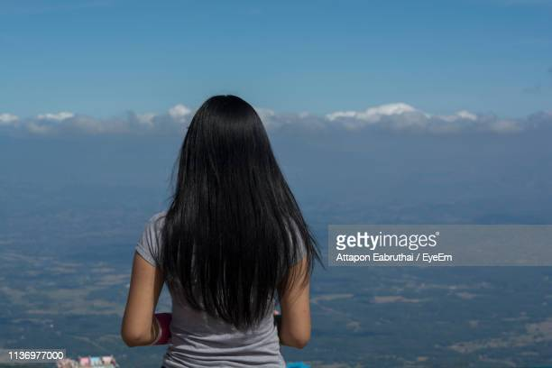 rear view of woman with long black hair looking at mountains - cheveux noirs photos et images de collection