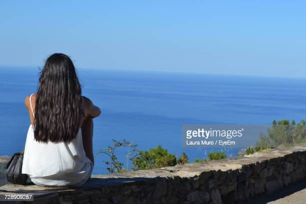 rear view of woman with long black hair sitting against sea and clear blue sky - muro stock photos and pictures