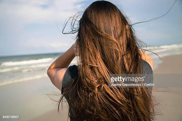 Rear View Of Woman With Long Brown Hair On Beach