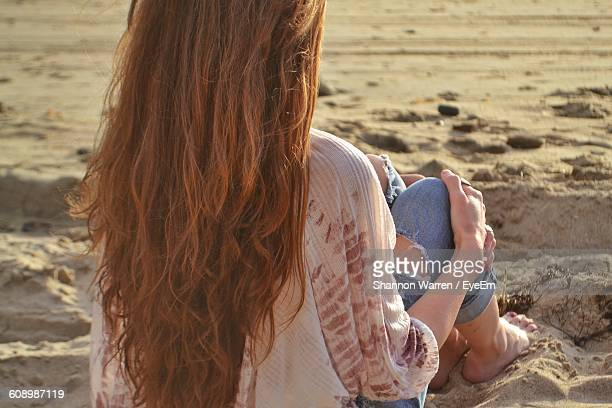 Rear View Of Woman With Long Brown Hair Sitting On Sand At Beach
